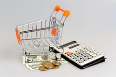 Shopping cart, money and calculator on gray Royalty Free Stock Images