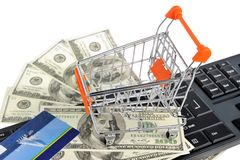 Shopping cart with money, credit card on keyboard Royalty Free Stock Photography
