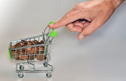 Shopping cart with money. Hand pushing a shopping cart full of coins Royalty Free Stock Image