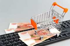 Shopping cart with money on keyboard on gray Royalty Free Stock Image