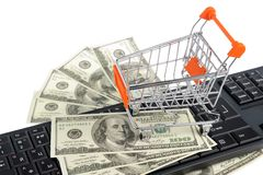 Shopping cart with money on keyboard isolated Royalty Free Stock Photos