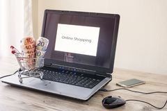 Shopping cart with money on the laptop. And a cellphone Royalty Free Stock Photos