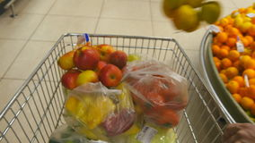 Shopping cart moving through aisles of shop, hands of people put there fruit and vegetables. Supermarket trolley with. Goods on the background of the market stock footage