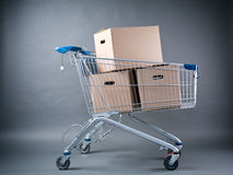 Shopping Cart with Moving Boxes. A stack of moving carton boxes in a shopping cart over a dark background Royalty Free Stock Images