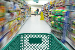 Shopping cart moving through supermarket Royalty Free Stock Photography