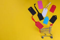 A shopping cart with multi-colored tags and price tags on a bright yellow background of a black Friday concept. shopping. view fro. M above. with place for stock photos