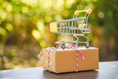 Shopping cart on nature green bokeh background Shopping cart on packing cardboard box prepare parcel box royalty free stock image