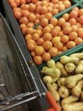 Shopping cart near fruit department. Close-up photohraph of shopping cart next to fruit department Stock Photos