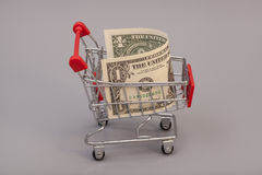 Shopping cart with one dollars Royalty Free Stock Photography