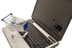 Miniature shopping cart on laptop computer. Miniature metal shopping cart on keyboard of laptop computer isolated on white Stock Photos