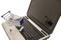 Miniature shopping cart on laptop computer Stock Photos