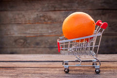 Shopping cart with orange on the old wood background. Royalty Free Stock Image