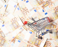 Shopping cart over the bank note bills Royalty Free Stock Images