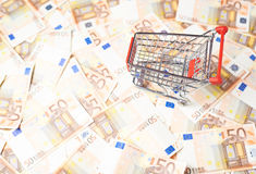 Shopping cart over the bank note bills Royalty Free Stock Image