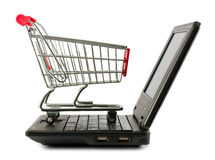 Shopping cart over a laptop Stock Images