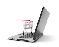 Shopping cart over a laptop computer isolated Royalty Free Stock Photos