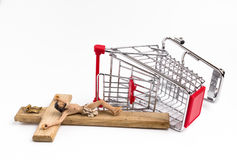 Shopping cart overturned with crucifix on the ground Royalty Free Stock Photos