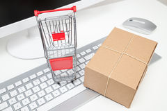 Shopping cart and package on keyboard Stock Images