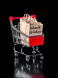 Shopping cart with paper bags is isolated on black background Royalty Free Stock Images