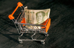 Shopping cart with a paper banknote of One Chinese Yuan and face of leader Mao, as a symbol of the modern economy Stock Photos