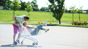Shopping cart on parking. A couple of newlyweds ride in a shopping basket near a supermarket. Fun, joke, joy, sense of stock video