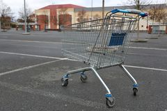 Shopping cart in the parking lot outside the shop stock image