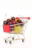Shopping cart with plum and cherry Stock Images