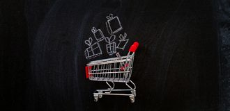 Shopping cart and presents on chalkboard. Stock Photo