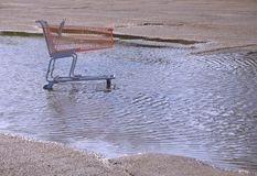 A shopping cart in a puddle. An exterior scene of an abandoned shopping cart in a puddle of water. This scene can work as a background or illustration for a Stock Photography