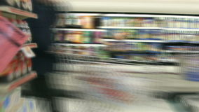 Shopping cart racing through grocery aisles in time lapse stock video
