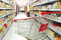 A shopping cart ready for purchase. Supermarket interior, empty red shopping cart Royalty Free Stock Image