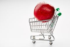 Red apple and shopping cart trolley Royalty Free Stock Photo
