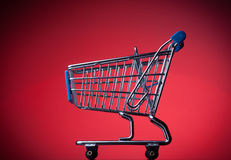 Shopping cart on red background Stock Photos