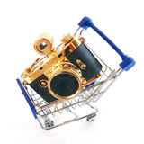Shopping cart with retro gold camera Royalty Free Stock Image
