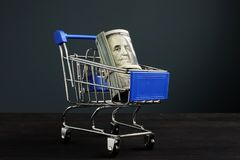 Shopping cart and roll of dollars. Money for loan and borrow cash. Concept royalty free stock photo