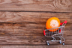 Shopping cart with rotten orange on the old wood background. Mold on food. The concept of selling spoiled food. Royalty Free Stock Photography