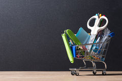 Shopping cart with school supplies over chalkboard background Royalty Free Stock Photo