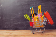 Shopping cart with school supplies over chalkboard background. Back to school sale concept Stock Image