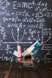 Shopping cart with school supplies, on the table against the background of a chalkboard. Concept back to school preparation. Shopping cart with school supplies royalty free stock image