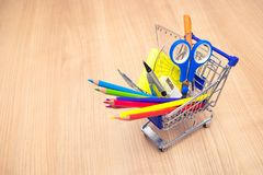 Shopping cart with school supplies on table . Back to school concept stock photography