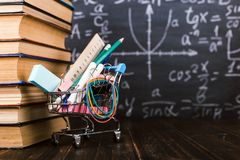 Shopping cart with school supplies, on the table with books against the background of a chalkboard. Concept back to school. Shopping cart with school supplies stock photography