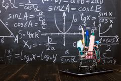 A shopping cart with school supplies on tablet, on table against background chalkboard. Concept back to school preparation and. A shopping cart with school royalty free stock photography