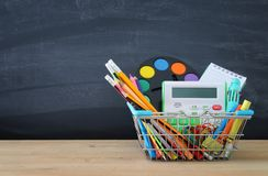 Shopping cart with school supply in front of blackboard. Back to school concept. royalty free stock image