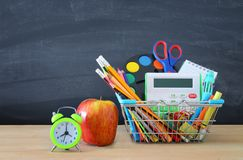 Shopping cart with school supply in front of blackboard. Back to school concept. royalty free stock images