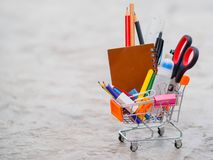 Shopping cart with school supply. stock image