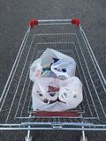Shopping cart with shopping bags Royalty Free Stock Photo