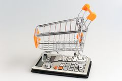 Shopping cart situated on calculator on gray Stock Image