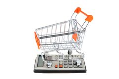 Shopping cart situated on calculator isolated Royalty Free Stock Images
