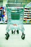 Shopping cart in store. Empty shopping cart in big store with products and few people in background. Shop concept Royalty Free Stock Images
