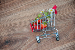 Shopping cart with strawberries inside on wooden background. Top view Royalty Free Stock Photography